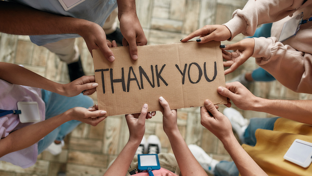 Top view of diverse young volunteers holding card with Thank you lettering while standing in charitable organization office, Selective focus on hands and inscription, Web Banner